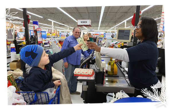 young child handing twenty dollar bill to cashier in store check out