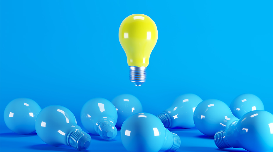 Yellow lightbulb in a sea of blue ones representing new digital solution ideas