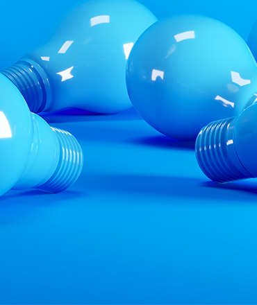 Close up of four blue light bulbs laying on a blue floor.