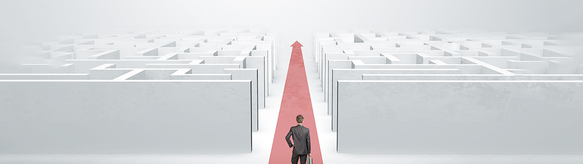 A person in a suit standing alone at the entrance of large, complex white maze with a straight red arrow guiding them forward representing a straightforward path of a good digital experience for b2b buyers.