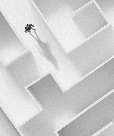 A person, alone, walking in the middle of complex, white maze representing a poor digital experience for b2b buyers