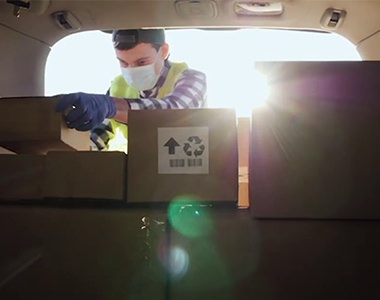 Video screenshot of man putting cardboard boxes in trunk of car