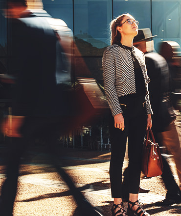 Woman looking up surrounded by blurred passerby's as she considers the brand promise of her company.