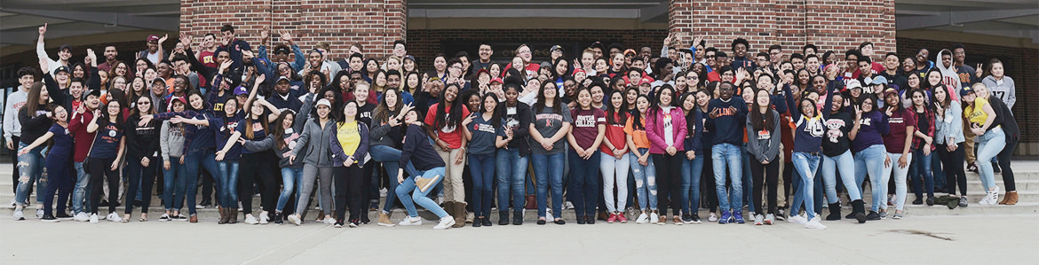 A large group of 30 plus adolescents representing the diversity of the students in the Chicago Scholars. The teens are smiling, hugging, and overall excited to be scholars.